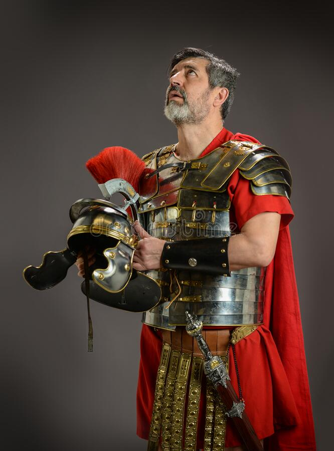 Roman soldier looking up while holding his helmet royalty free stock images