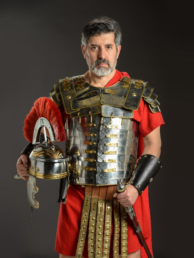 Roman soldier posing holding his helmet stock images