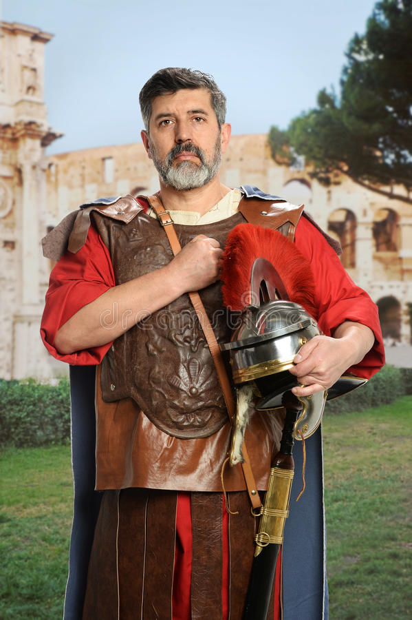 Roman Soldier Saluting. With fist on chest over colosseum in background royalty free stock photography