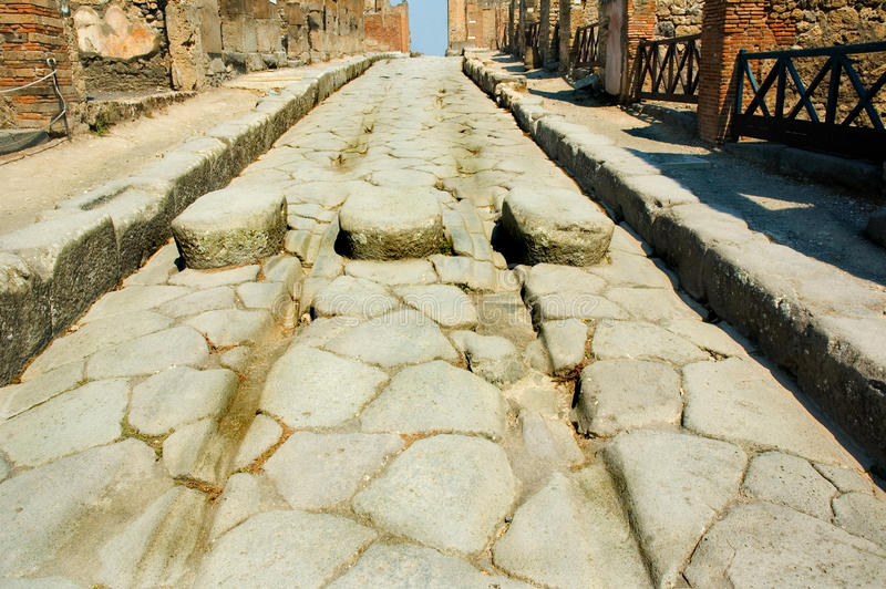 Roman street in Pompeii. With chariot grooves in the stone and stepping stones for pedestrians royalty free stock images