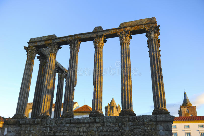 Roman temple of Diana and the dome of Cathedral at sunset, Evora, Portugal stock photography