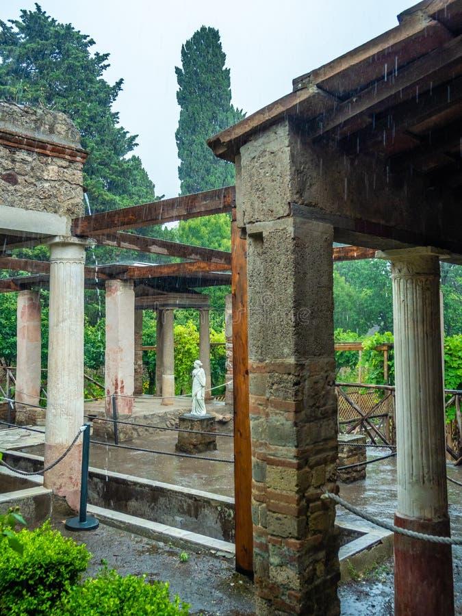 Roman villa in Pompeii, Italy. World Heritage List. Heavy rain in garden of ruined Roman villa in the ancient Roman city of Pompeii, near modern Naples in Italy royalty free stock photos