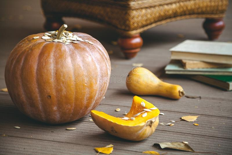 Romance of autumn. Pumpkins and stack of books on floor. Poetic autumn still life with a pumpkin. Ripe pumpkins of different shapes, seeds and a stack of books stock photo