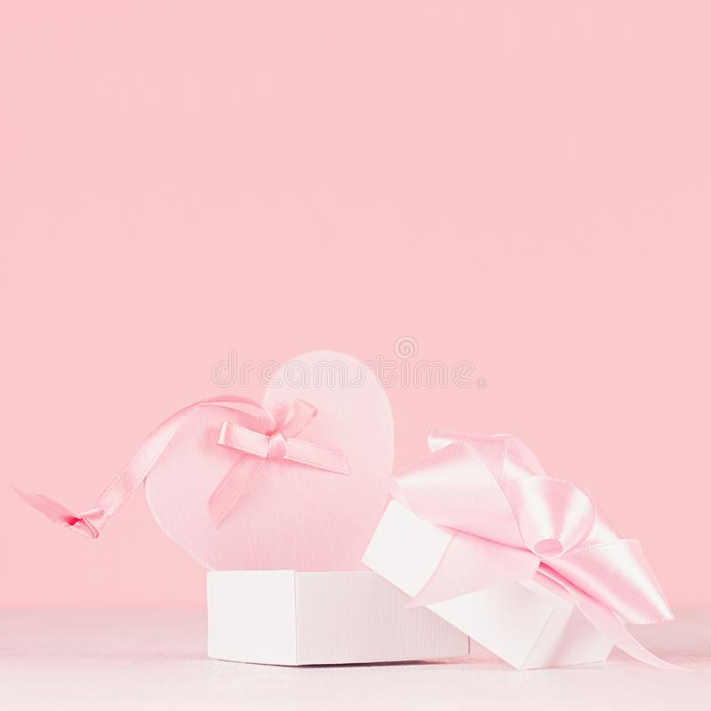 Romance celebration background for Valentine and wedding - cute heart with silk ribbon and gift on white wood board, closeup. stock image