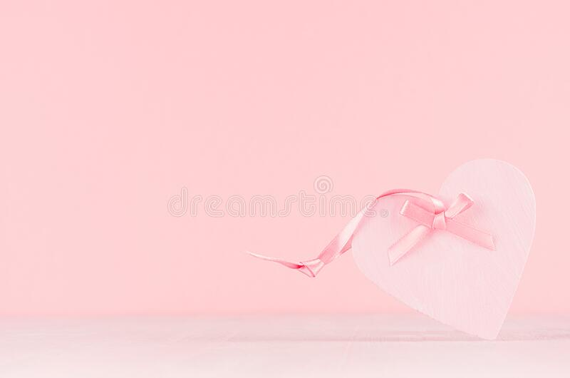 Romance festive background - delicate pink heart with gentle ribbon and bow on white wooden table, copy space. stock images