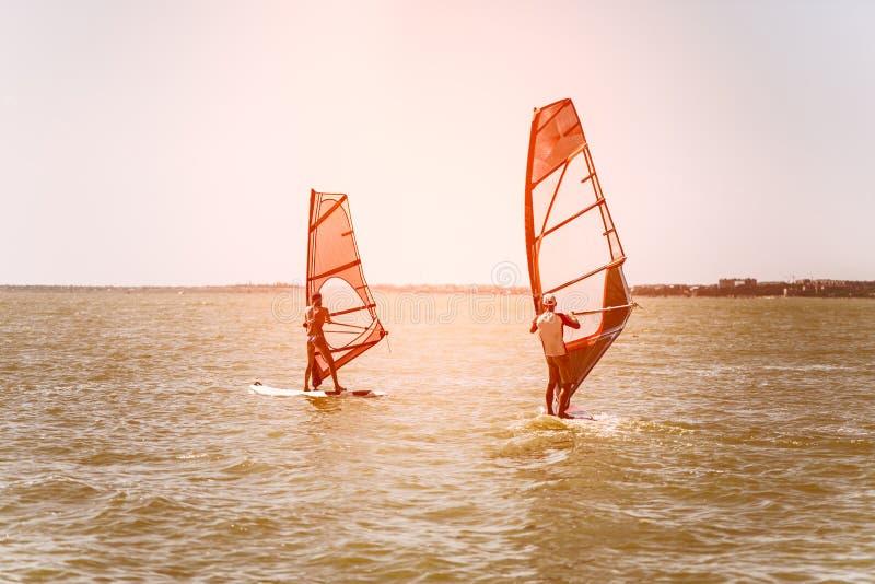 Romance im Seepaarmann und -frau, die zusammen auf ein Windsurfenbrett während im Urlaub im Süden segeln stockfoto