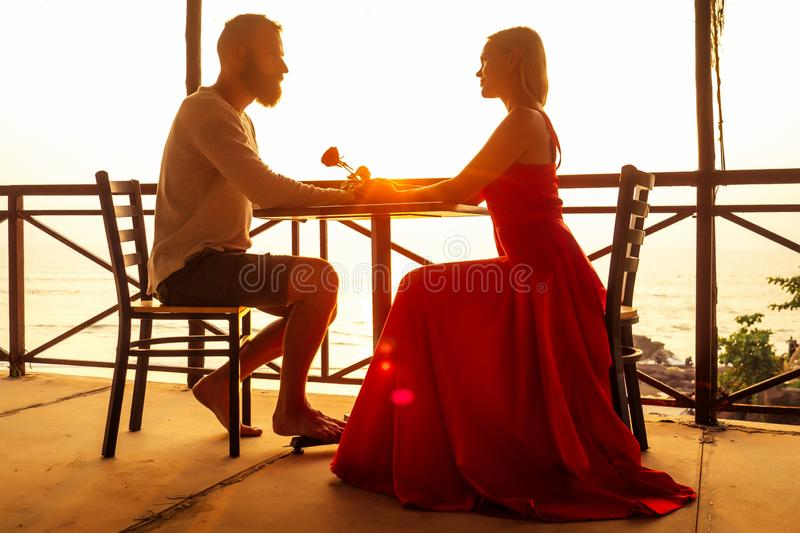 Romance marriage proposal by the sea tropical paradise beach beachfront restaurant.a man in a white shirt and a stock photos