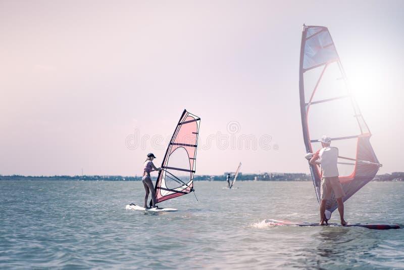 Romance no homem e na mulher dos pares do mar que navegam junto em uma placa do windsurfe quando em férias no sul imagens de stock