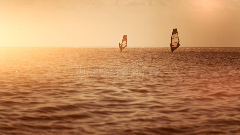 Romance no homem e na mulher dos pares do mar que navegam junto em uma placa do windsurfe quando em férias no sul imagem de stock