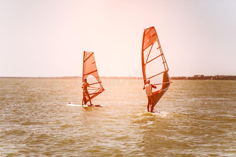 Romance no homem e na mulher dos pares do mar que navegam junto em uma placa do windsurfe quando em férias no sul foto de stock
