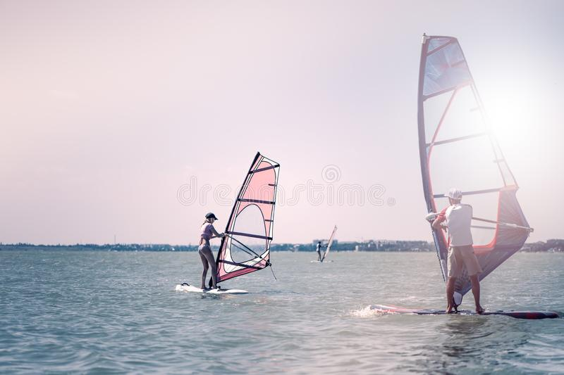 Romance in the sea couple man and woman together sailing on a windsurfing board while on vacation in south stock images
