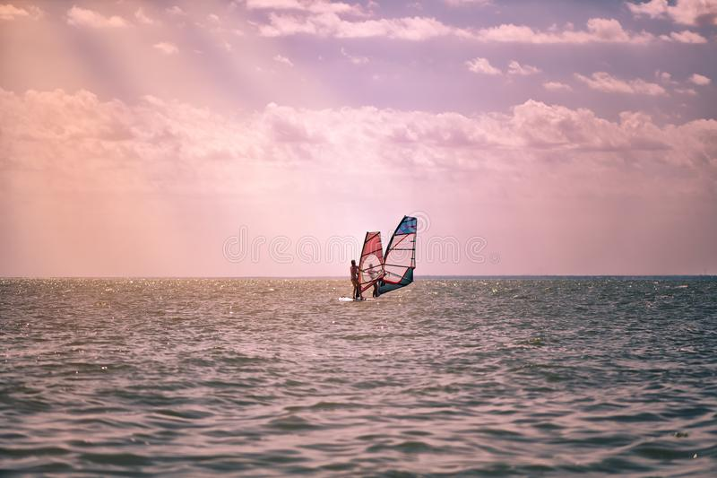 Romance in the sea couple man and woman together sailing on a windsurfing board while on vacation in south stock photography