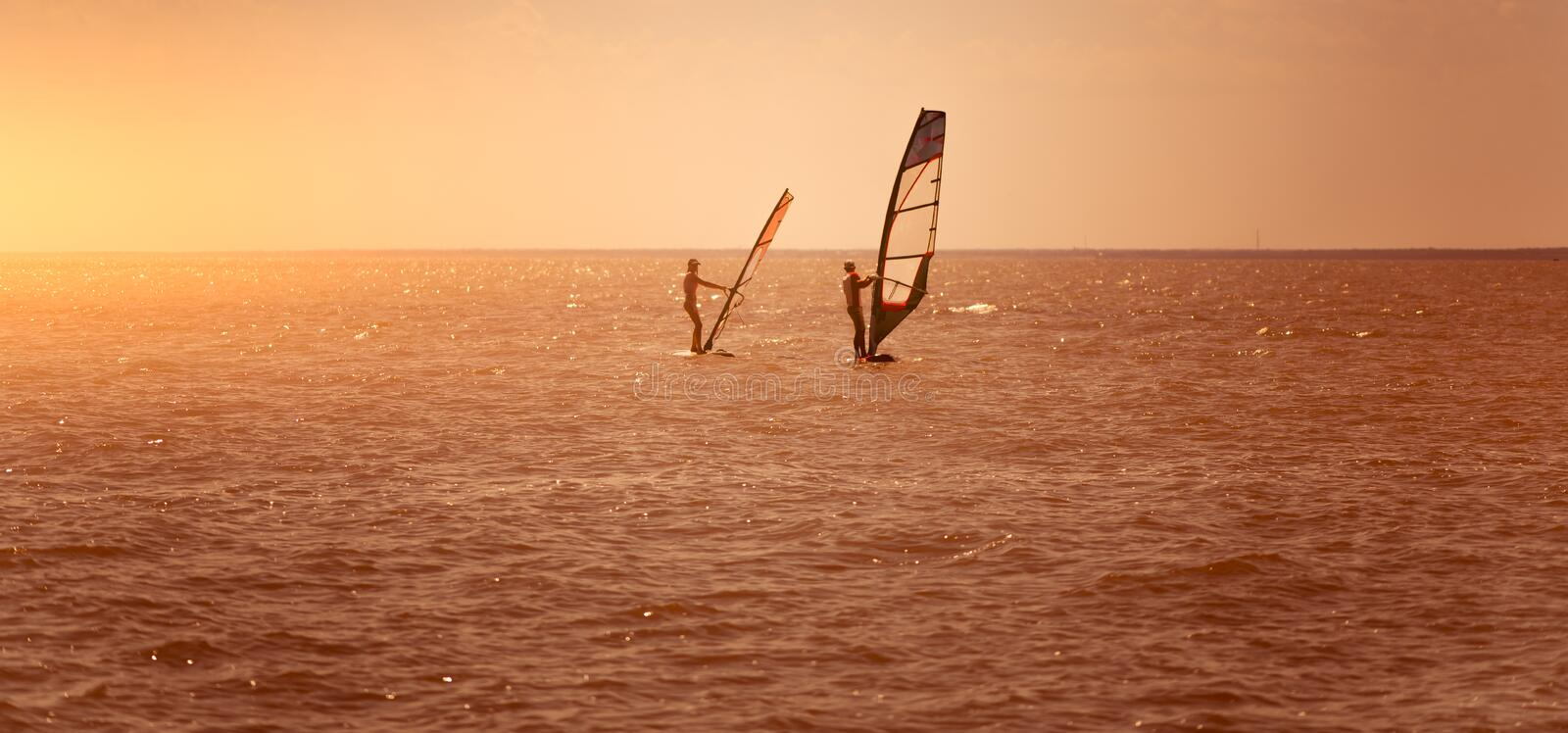 Romance in the sea couple man and woman together sailing on a windsurfing board while on vacation in south stock photos