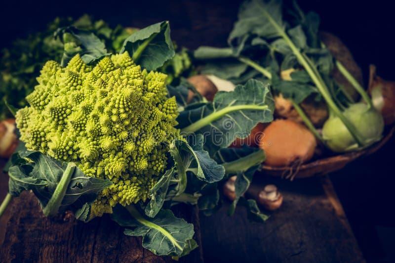 Romanescobloemkool op rustieke keukenlijst met groenten over houten achtergrond stock afbeeldingen