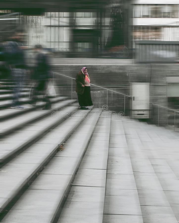 Romani woman standing in a blurred vision of city life. Romani woman standing still in a blurred vision of urban everyday life stock photo