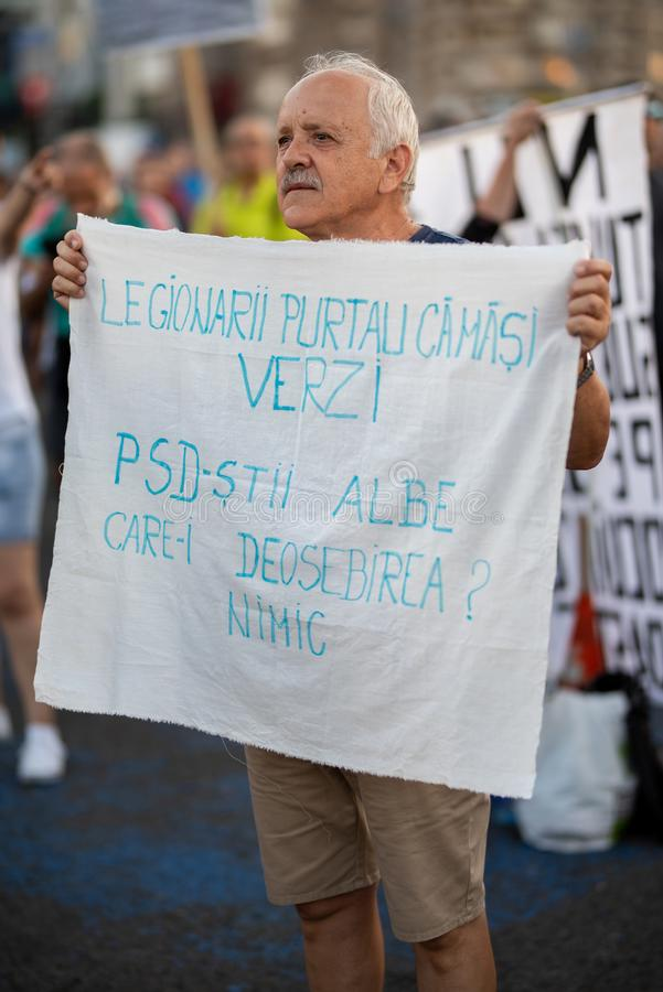 Romania, Bucharest - August 12, 2018: Old man protesting peacefully. While holding its anti government sign stock photography