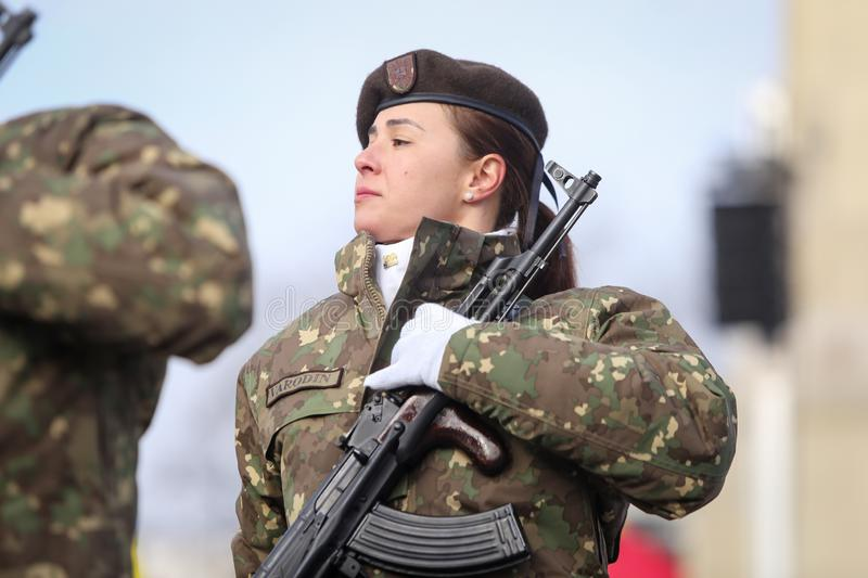 Romanian army female soldier is armed with AK-47 assault rifles stock images
