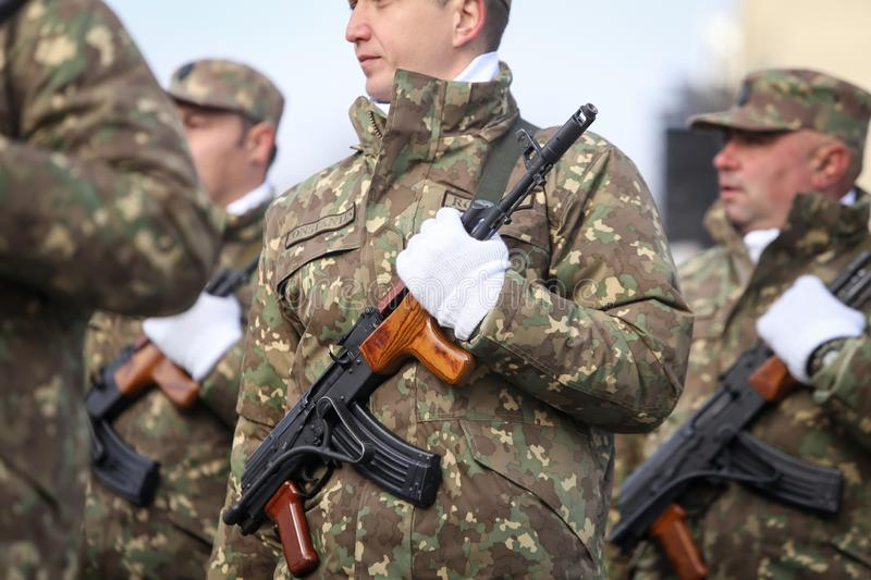 Romanian army soldiers are armed with AK-47 assault rifles. Bucharest, Romania - December 1, 2018: Romanian army soldiers, armed with AK-47 assault rifles, take stock photos