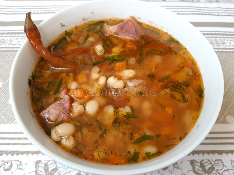 Romanian Bean Soup with Smoked Pork Meat. Fasole cu ciolan afumat royalty free stock image