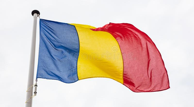 Romanian flag waving against cloudy sky background stock image