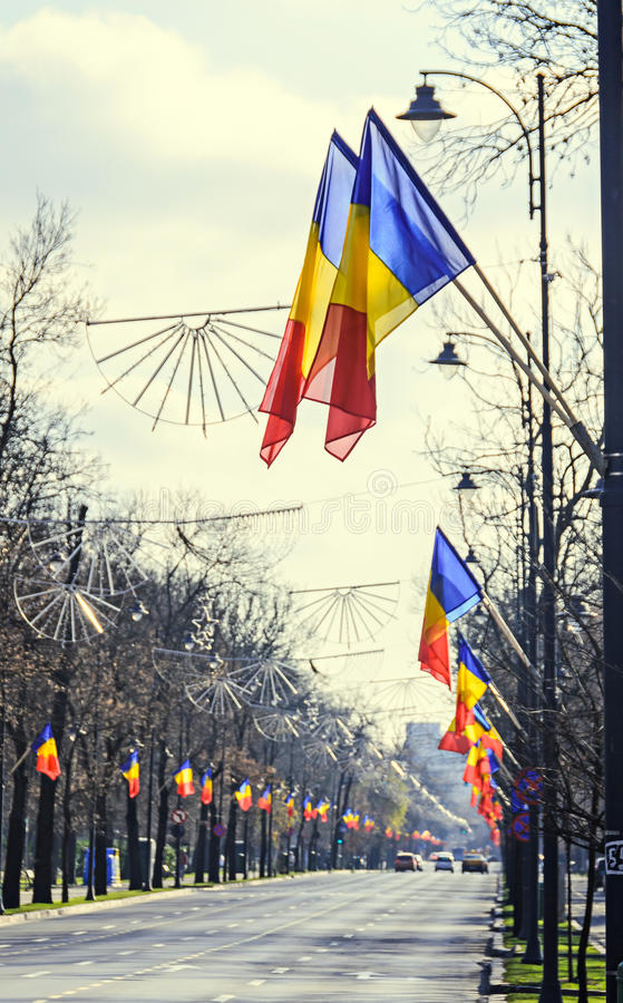 Romanian Flags in the sun, National Day of Romania. Blue sky close up stock image