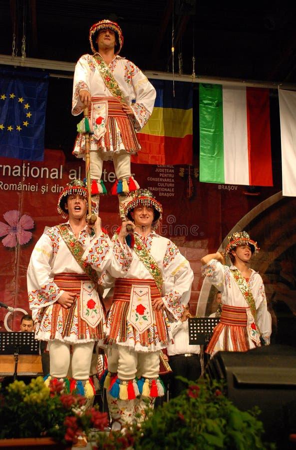 Romanian folk dancers at an international festival. Romanian men folk dancers from a Romanian traditional dance ensemble - called POIENITA, dancing at the royalty free stock photo