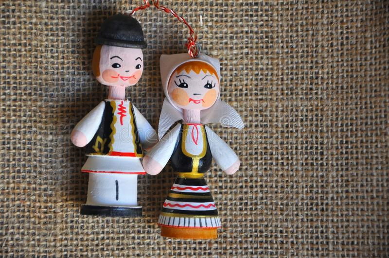 Romanian man and woman. Dolls representing Romanian traditional costumes on a linen cloth stock image