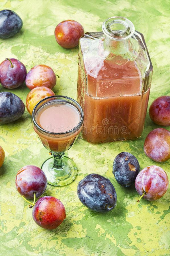 Romanian national plum liquor. Slivovitsa-plum brandy.Slivyanka,strong alcoholic drink made from ripe plums royalty free stock image
