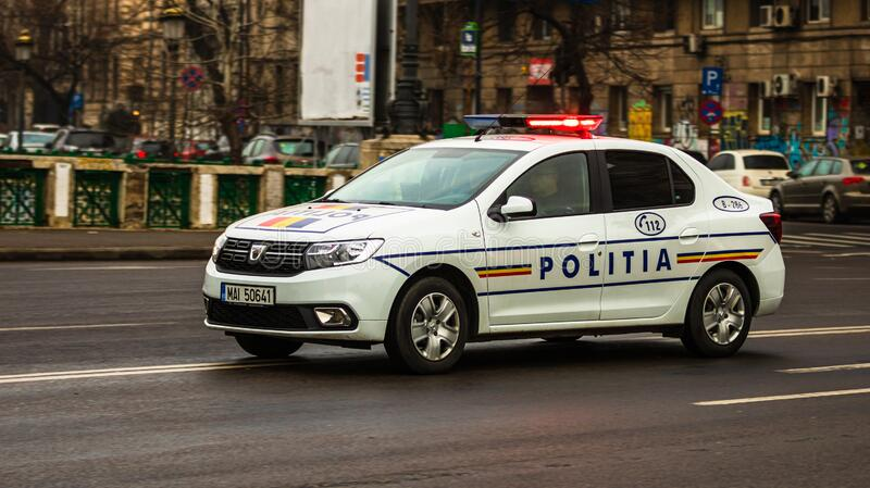 Romanian police (Politia Rutiera) car with the lights flashing patrolling streets to avoid curfew breaches amid the spread of the. COVID-19 in downtown stock photo
