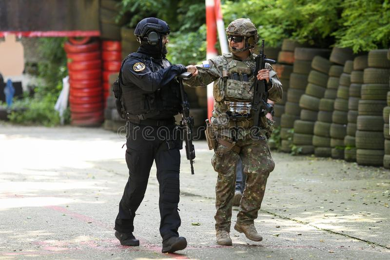 A Romanian SIAS equivalent of SWAT in the US police officer and a special forces soldier train together in a shooting range royalty free stock images