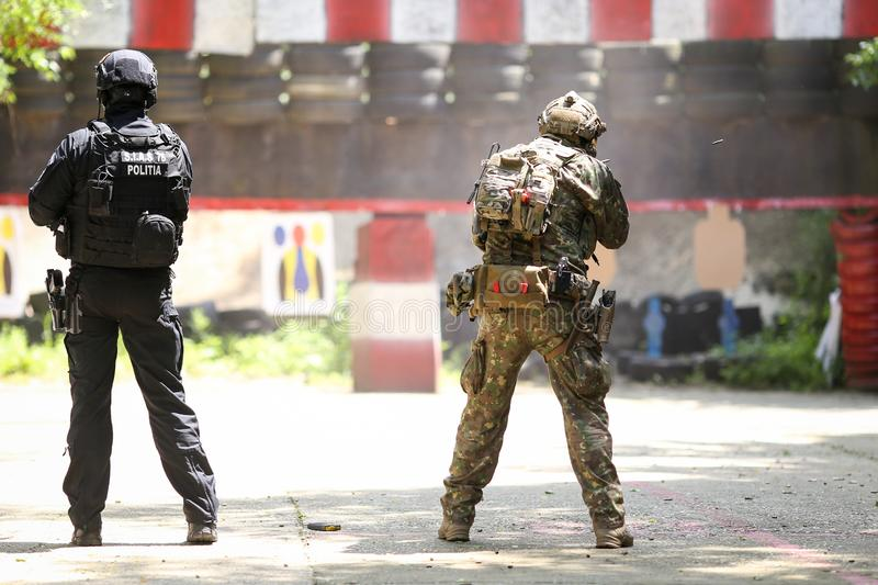 A Romanian SIAS equivalent of SWAT in the US police officer and a special forces soldier train together in a shooting range stock images