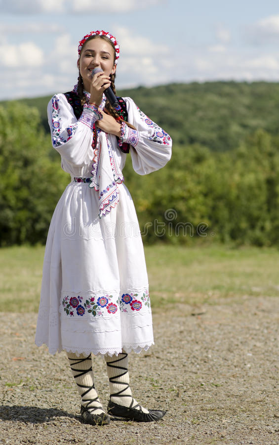 Romanian singer Alexandra Chira. ROMANIA, Doh village -august 14, 2014: Romanian singer Alexandra Chira and his band in background in traditional costume