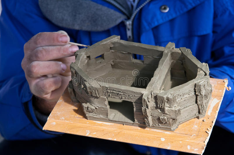 Romanian traditional peasant model house. Here we can see how a potter is making a romanian traditional peasant model house with clay. Notice the textures and stock photos
