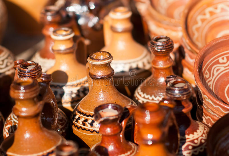 Romanian traditional pottery handcrafted mugs at a souvenir shop. Romanian traditional handcrafted pottery. Plates and jugs royalty free stock images