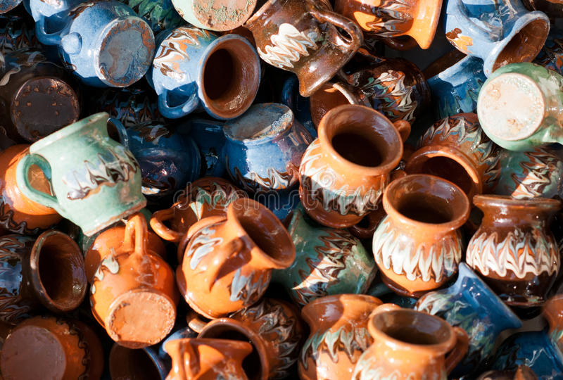 Romanian traditional pottery handcrafted mugs at a souvenir shop. Romanian traditional handcrafted pottery. Plates and jugs stock photography