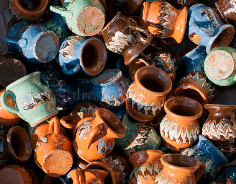 Romanian traditional pottery handcrafted mugs at a souvenir shop. Romanian traditional handcrafted pottery. Plates and jugs stock images