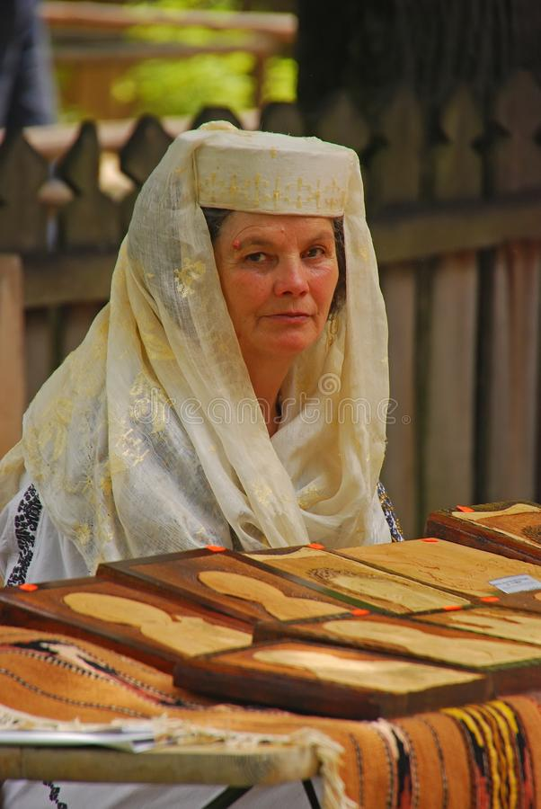 Romanian woman in traditional costume selling handicraft at local flea market stock image