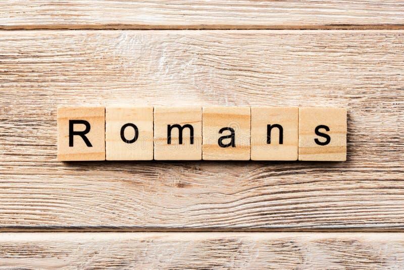 Romans formułują piszą na drewnianym bloku romans tekst na stole, pojęcie fotografia royalty free