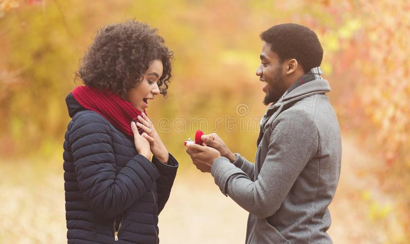 Romantic afro man proposing to woman in autumn park stock images