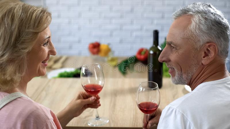 Romantic aged couple with wine glasses at home date, happy marriage, aperitif. Stock photo royalty free stock image