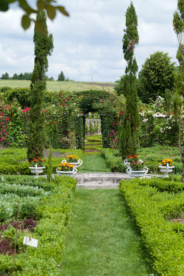 The romantic alley-way in the pergola from roses. Subtle and full taste garden and chateau La Chatonniere near Villandry. Loire Valley royalty free stock photo