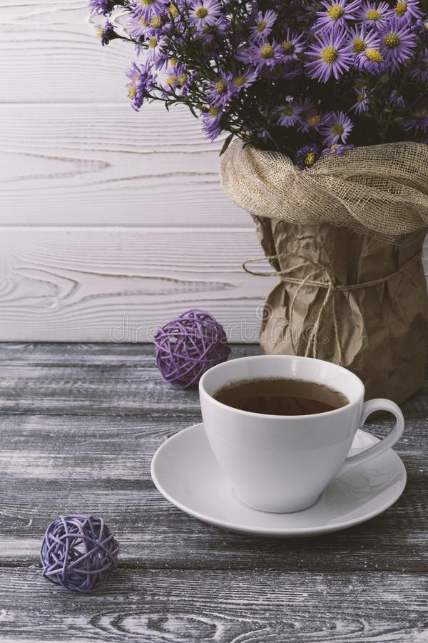 Romantic autumn composition with a cup of tea, lilac flowers in a vase on a gray wooden table. Autumnal concept royalty free stock photo