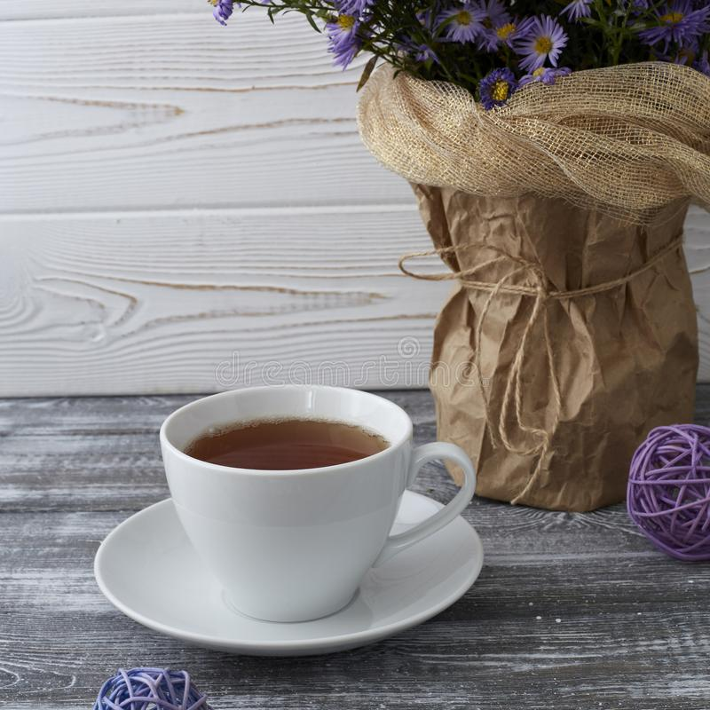 Romantic background with a cup of tea, lilac flowers in a vase on a gray wooden table.  royalty free stock photo