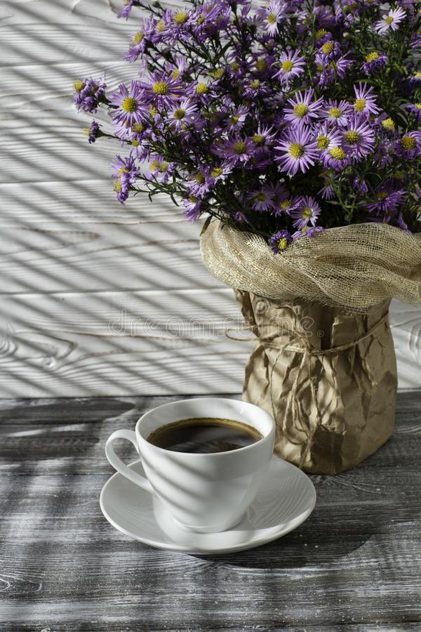 Romantic background with a cup of tea, lilac flowers in a vase on a gray wooden table.  stock image