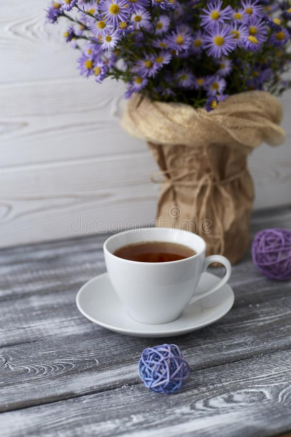 Romantic background with a cup of tea, lilac flowers in a vase on a gray wooden table.  stock photo