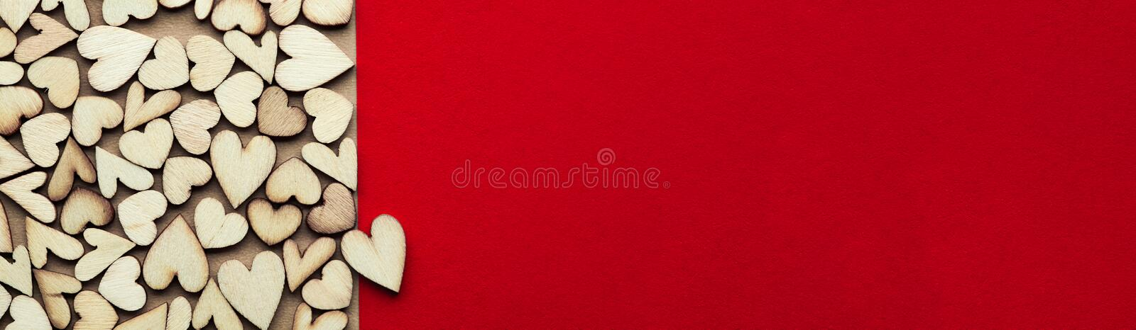 Romantic background of dozens of tiny wooden hearts with a single heart on a red card. For love, romance, or Valentine`s Day. With blank space for text royalty free stock photo