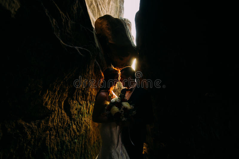 Romantic beautiful bride and elegant stylish groom in darkened rock cleft backgrounded by sunset shining stock image