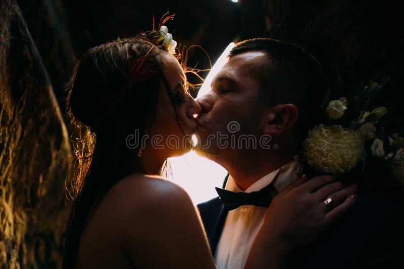 Romantic beautiful bride and elegant stylish groom kissing, backgrounded by sunset shining. Close-up stock photos