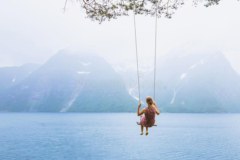 Girl on swing in Norway, happy dreamer, inspiration background royalty free stock image