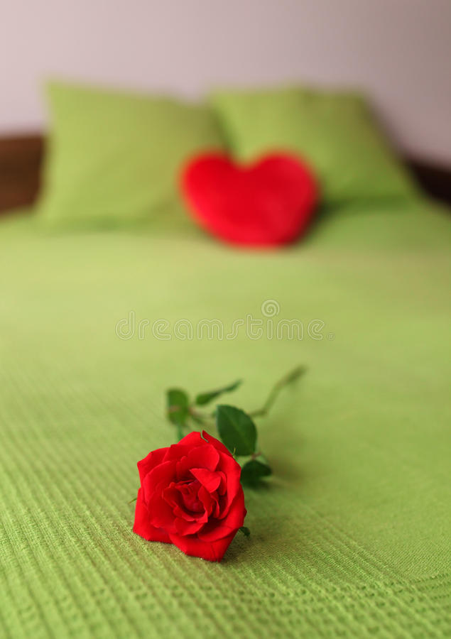 Romantic bed. Double bed with heart shape pillow and red rose stock photo
